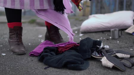 poorness : Homeless rummaging in clothes scattered on the street. Close up.