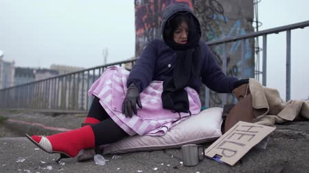 poorness : Homeless woman appreciate the shoes worn on a thick red sock and looks at the jacket appreciatively. Stock Footage