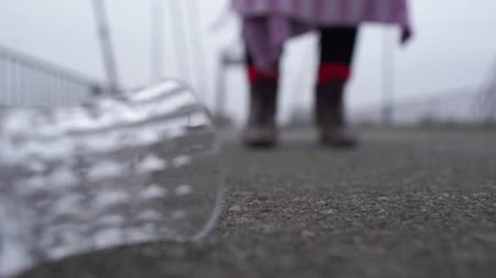 poorness : Close-up of a glass lying on the pavement. Confidential figure of an old woman in tatters walking on a blurred background. Focus moves from the foreground to the background with the dirty shoes of the homeless