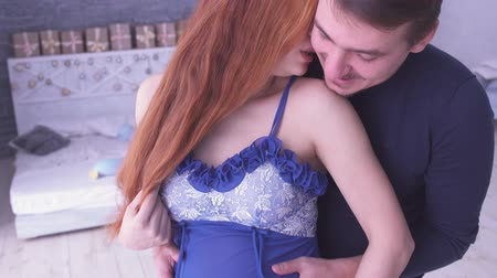 cosiness : Beautiful redhead pregnant woman and her husband stand near each other. Mom and dad hands on pregnant tummy. Maternity concept. Pregnancy. Happy family.