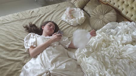 rainha : Beautiful woman in white vintage ball costume lying on the huge golden bed with feather fan and hat while talking buy mobile phone