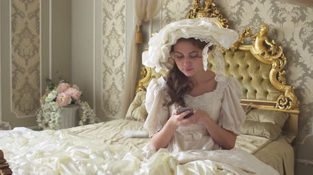 uykulu : Cute young woman in ball gown sitting on the gold decorated bed and texts on cell phone using gadget