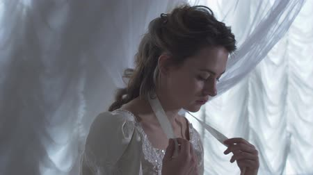 kraliçe : Young beautiful woman sitting arround white net curtains and unties a ribbon on her neck Stok Video