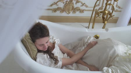 косплей : Young woman in white wedding dress lying in the amazing modern ampty bath and sleep on the pillow Стоковые видеозаписи