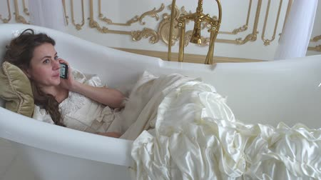 rainha : Cute young woman lying in the ampty bath on the soft pillow and talking by cell phone with feather fan in hands