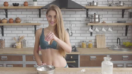 raflar : Portrait young woman in lingerie takes a pinch of flour and pours into a bowl in the kitchen. Sensual girl cooking at home Stok Video