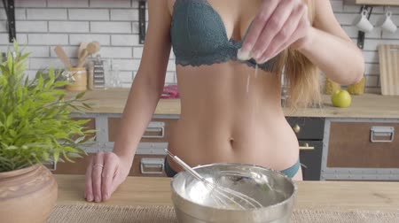 raflar : Woman with a perfect body in lingerie takes a pinch of flour and pours into a bowl in the kitchen close up. Unrecognizable girl cooking at home.