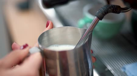 ristretto : Milk poured into a metal mug from a coffee machine. Close up