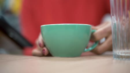 cheerfulness : Hands of office worker puts blue cup on the table close up Stock Footage