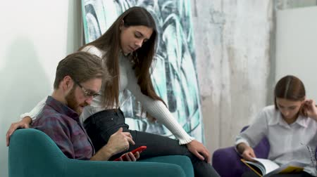 armchairs : Colleagues having a break. Woman is study papers, bearded man and lady with long hair are flirting