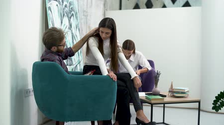sedução : Colleagues having a break. Bearded man removes hair from a girl shoulder, flirting