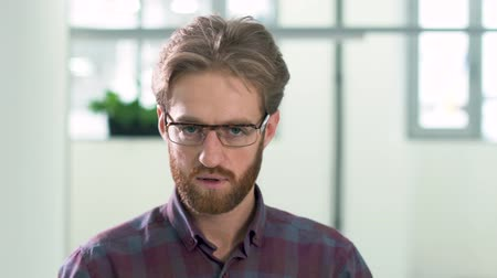 attitude : Portrait of bearded man looking in camera with sadness and anger close up Stock Footage