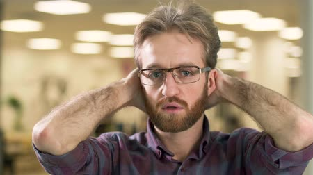 тревожный : Portrait of young attractive serious bearded guy in glasses preoccupied with a difficult problem. Стоковые видеозаписи