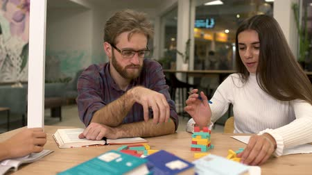 dinlenmek : Attractive bearded man with glasses and a cute girlfriend with long dark hair are building a tower of multi-colored wooden blocks while sitting at the table. Friends play an interesting strategy game.
