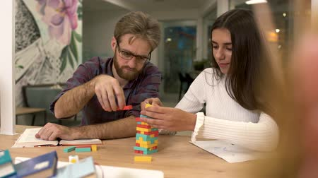 kırılganlık : Handsome bearded man with glasses and a cute girlfriend with long dark hair are building a tower of multi-colored wooden blocks while sitting at the table. Friends play an interesting strategy game. Stok Video