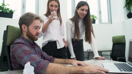 ситуация : A bearded guy and two young girls are discussing the work plan in the office in the workplace. The senior manager shows his ideas to his colleagues on the laptop screen.
