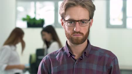 předstírat : Portrait of a bearded guy in glasses and in a casual plaid shirt standing in the office center in the lobby on the background of two girls office workers. The man smiles first and then becomes serious. Dostupné videozáznamy