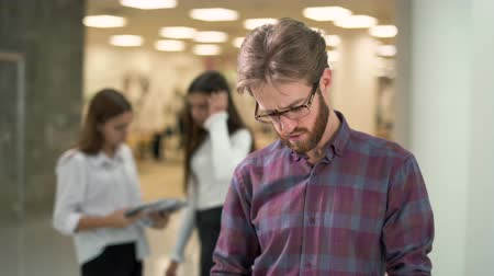 эффективный : Portrait a guy with a beard in glasses and casual plaid shirt reading documents with sales reports standing in the lobby of an office business center. Two girls colleagues on background.