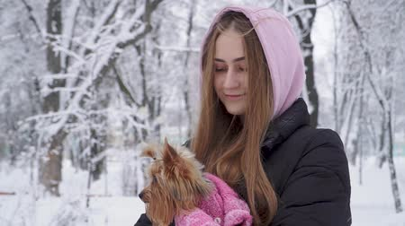 yorkie : Portrait lonely teen girl with long hair hugging a yorkshire terrier dressed in wool sweater holding dog on hands in a winter snow-covered park. Teenager and a dog on a walk outdoors. Snowing.