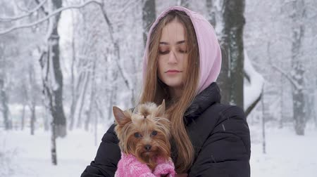 yorkie : Portrait lonely cute girl with long hair hugging a yorkshire terrier dressed in wool sweater holding dog on hands in a winter snow-covered park. Teenager and a dog on a walk outdoors. Snowing.
