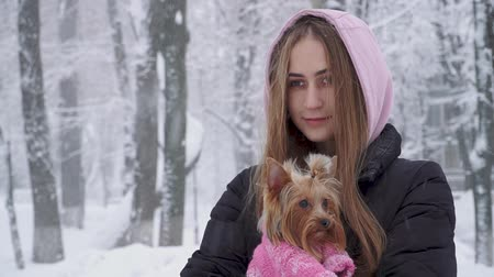 держит : Portrait smilling cute girl with long hair hugging a yorkshire terrier dressed in wool sweater holding dog on hands in a winter snow-covered park. Teenager and a dog on a walk outdoors. Snowing.