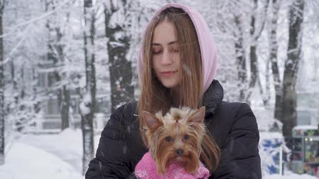yorkie : Portrait smilling cute girl with long hair hugging a yorkshire terrier dressed in wool sweater holding dog on hands in a winter snow-covered park. Teenager and a dog on a walk outdoors. Snowing.