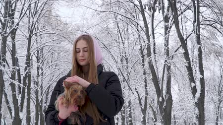 yorkie : Portrait teen girl holding a yorkshire terrier on hands on a background of snow covered trees in a winter park. A teenager and a pet on a walk outdoors. Slow motion.