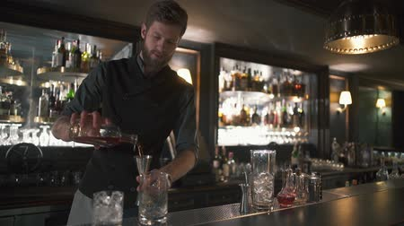 shaker : Tall bearded bartender pouring rum in the metal jar, then in glass. Barman making cocktail in modern bar with many bottles on shelves Stock Footage