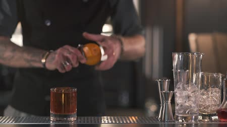 shaker : Unrecognizable bartender cuts off the orange zest to make a refreshing alcoholic cocktail stands on the bar counter in modern pub. Slow motion