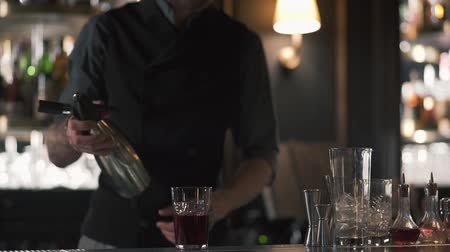 насилие : Hipster bartender using shaker and making an alcohol cocktail in beautiful modern bar. Slow motion