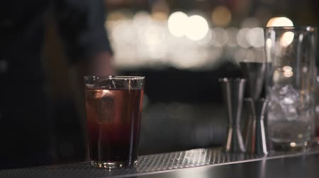 bêbado : Glass with sparkling cold alcohol cocktail or whiskey with cube ice for refreshing made in bar by bartender. Close up Stock Footage