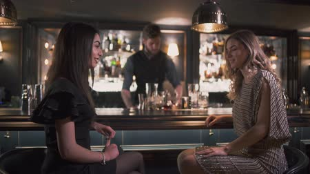 chill out : Bartender serving cocktails to pretty girls while the are chatting and smiling at the modern good bar Stock Footage
