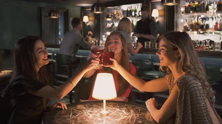 uzakta bakıyor : Three happy women sitting at the small table in bar close up. Girls have celebration together, they clink glasses and look in camera smiling. Lonely ladies have a fun Stok Video