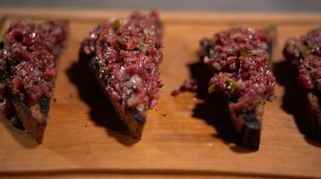 тощий : Sandwiches of grilled brown bread with minced meat serving on wooden board in restaurant. Close up.