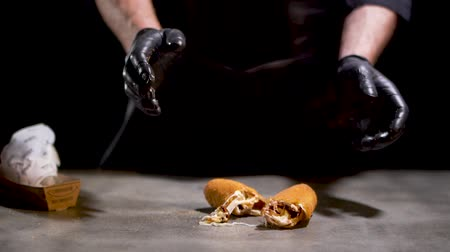 utěšený : Unrecognized chef in black rubber gloves throws two pieces of delicious grilled cheese bun on the table isolated on black background. Slow motion Dostupné videozáznamy