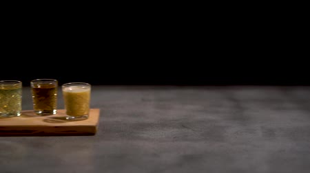 romênia : Female hand moves five different alcoholic shots coctails in small glasses on the desk. Close up slow motion.