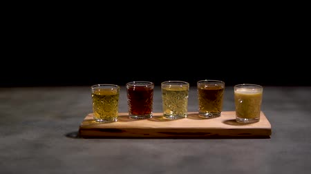 romênia : Close up five different alcoholic shots coctails in small glasses standing on the desk isolated on black background. Stock Footage