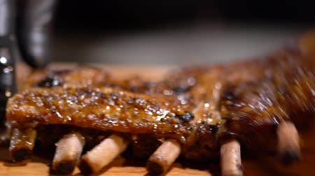 mouth watering : Just cooked juicy fragrant fried ribs throw on the elegant serving wooden table. Slow motion close up