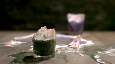 romênia : Two glasses with multi-colored alcoholic beverages collide on the table and break into fragments. Slow motion.