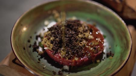olive oil pour : Tartar on the plate served in restaurant kitchen close up. Olive oil pours on the food Stock Footage