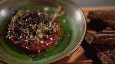 capers : Raw tartar with ingredients filled with olea, lying in a clay plate on a table next to black toasted bread close up.. The camera moves from left to right. Stock Footage