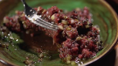 kapary : Close-up of the mixing of the tartare lying in a clay plate with a fork. Slow motion.