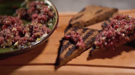 kapary : Preparation of toasts with tartar in restaurant kitchen close up. Small pieces of meat are falling