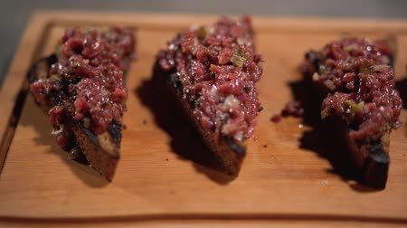 kapary : Toasts of grilled brown bread with minced meat serving on wooden board in restaurant. Camera moves from left to right.