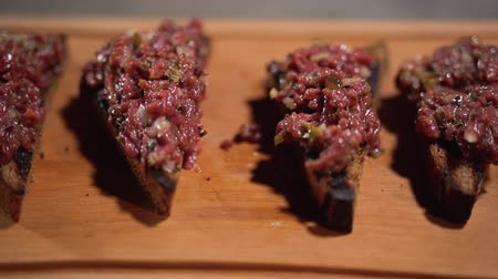 capers : Toasts of grilled brown bread with minced meat serving on wooden board in restaurant. The camera moves from right to left.