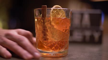 csipesz : Male hand moves alcohol shot with one piece of orange and cinnamon on the table close up Stock mozgókép