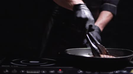 элита : Cook in black dress and gloves prepares meat for burger on the modern electric stove close up