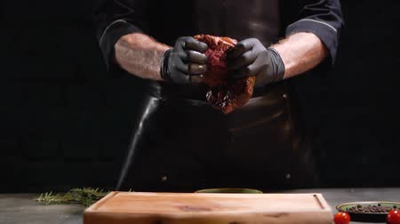 элита : Hands in black rubber gloves tears apart big piece of meat close up. Juice dripping on cutting board. Slow motion.