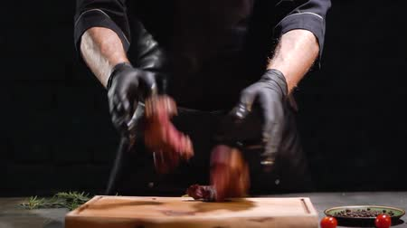 элита : Hands in black rubber gloves throw two pieces of meat on the cutting board close up. Slow motion. Close up.