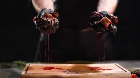 seçkinler : Hands in black rubber gloves squeeze two pieces of meat close up. Juice dripping on cutting board.. Stok Video